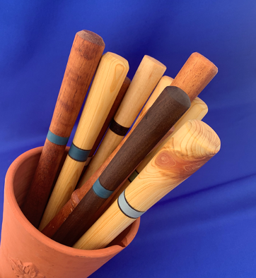 Spurtles in clay pot on blue background